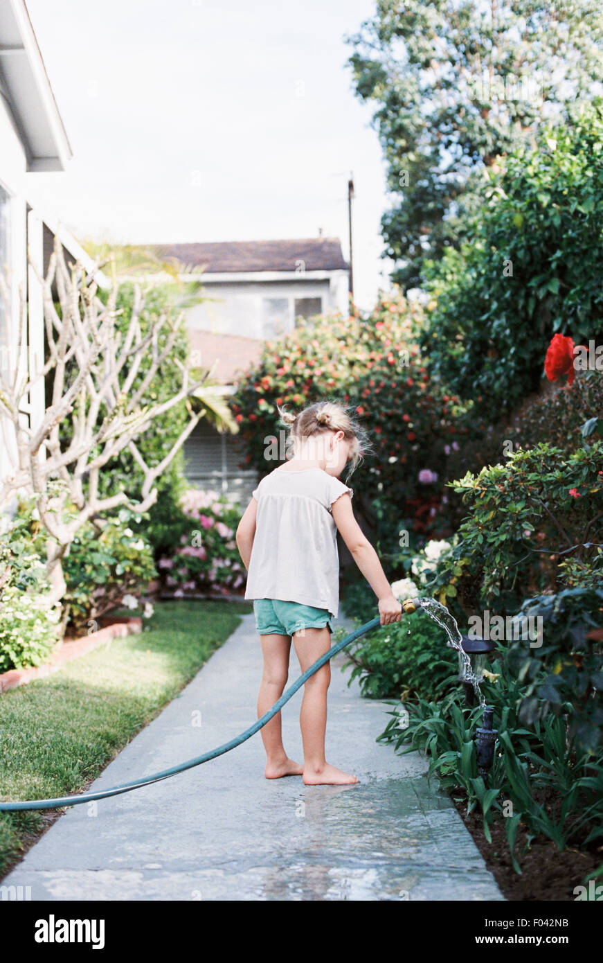 Young girl standing on a path in a garden, playing with a water hose. - Stock Image