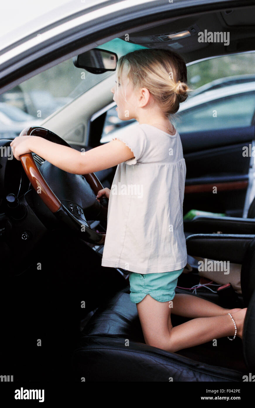 Young girl kneeling on the drivers seat of a car, holding the steering wheel, pretending to drive. - Stock Image