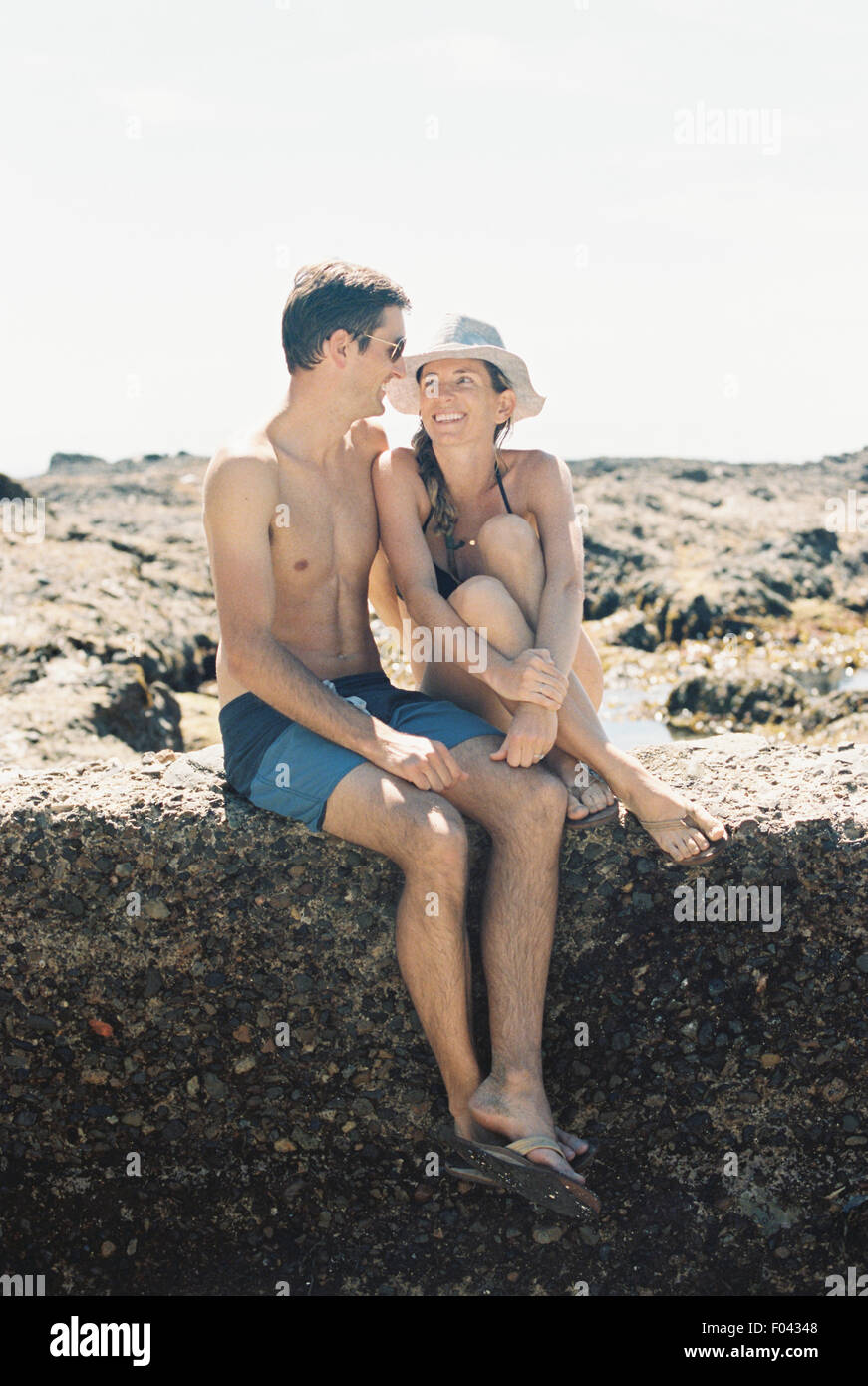 A man and woman, a couple sitting on the beach looking lovingly at each other - Stock Image
