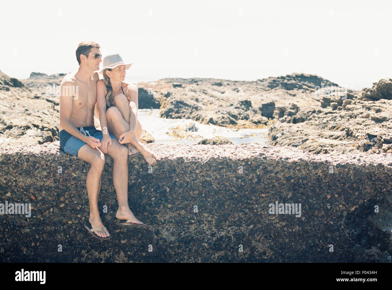 A man and woman, couple on the beach sitting on a wall by a rock pool. - Stock Image
