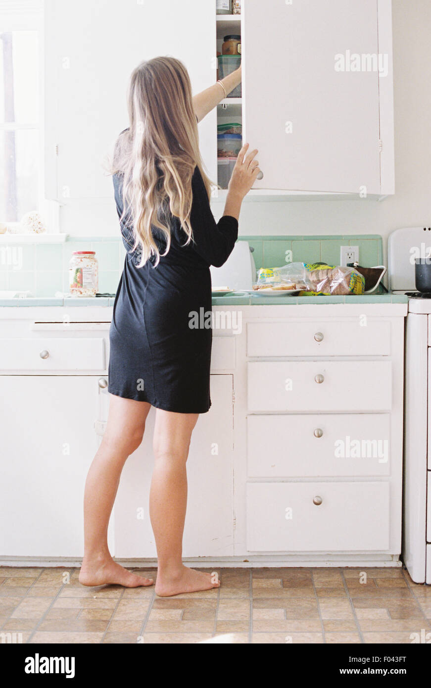 A woman with long blond hair standing barefoot in a kitchen, opening a cupboard. - Stock Image