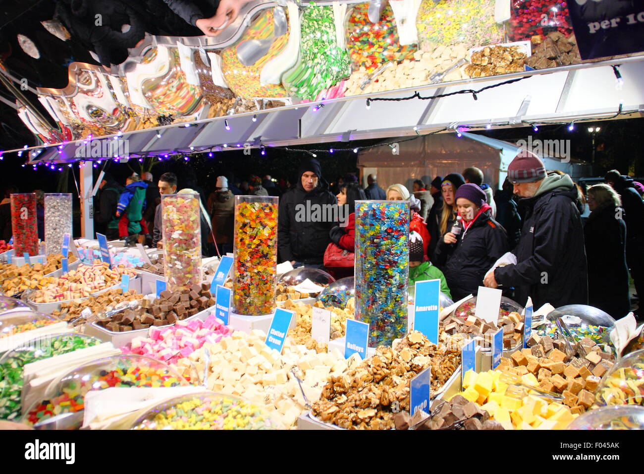 People peruse sweet treats on a confectionery stall at Lincoln Christmas Market, Lincolnshire England UK - Stock Image