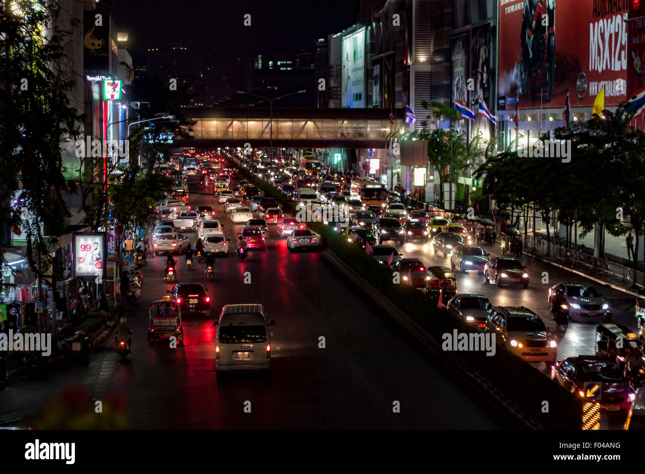 A busy street in Bangkok at night with long queues of stationary cars trying to get through city traffic. - Stock Image