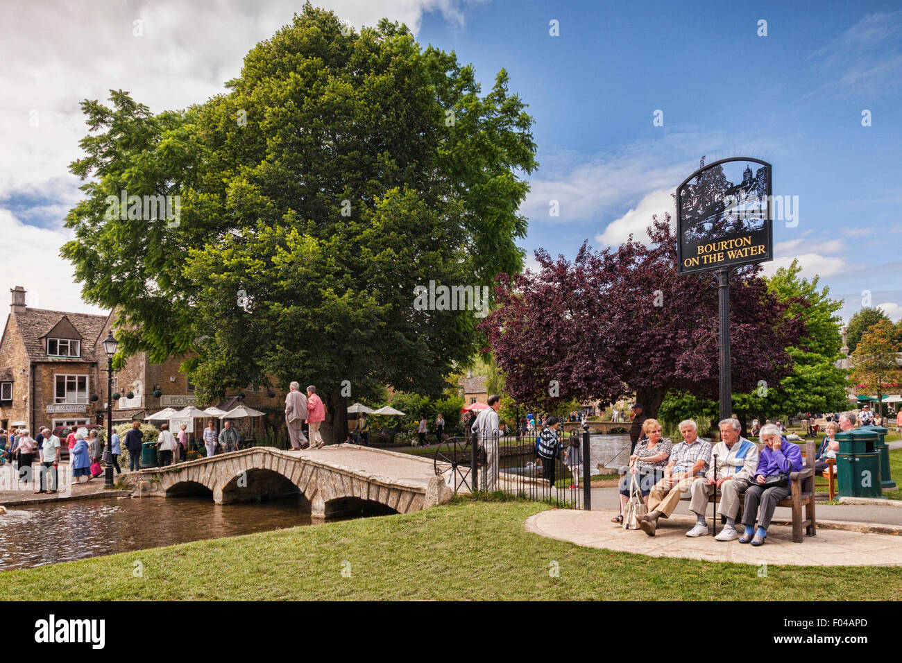 Tourists enjoy summer afternoon in the Cotswold village of Bourton-on-the-Water, Gloucestershire, England. Stock Photo