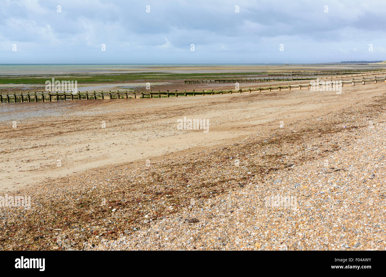 Deserted shingle beach at low tide. - Stock Image