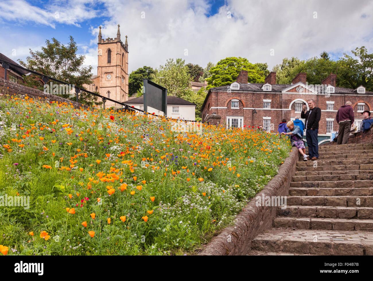 Tourists gather near the Iron Bridge in the village of Ironbridge, Shropshire, England - Stock Image