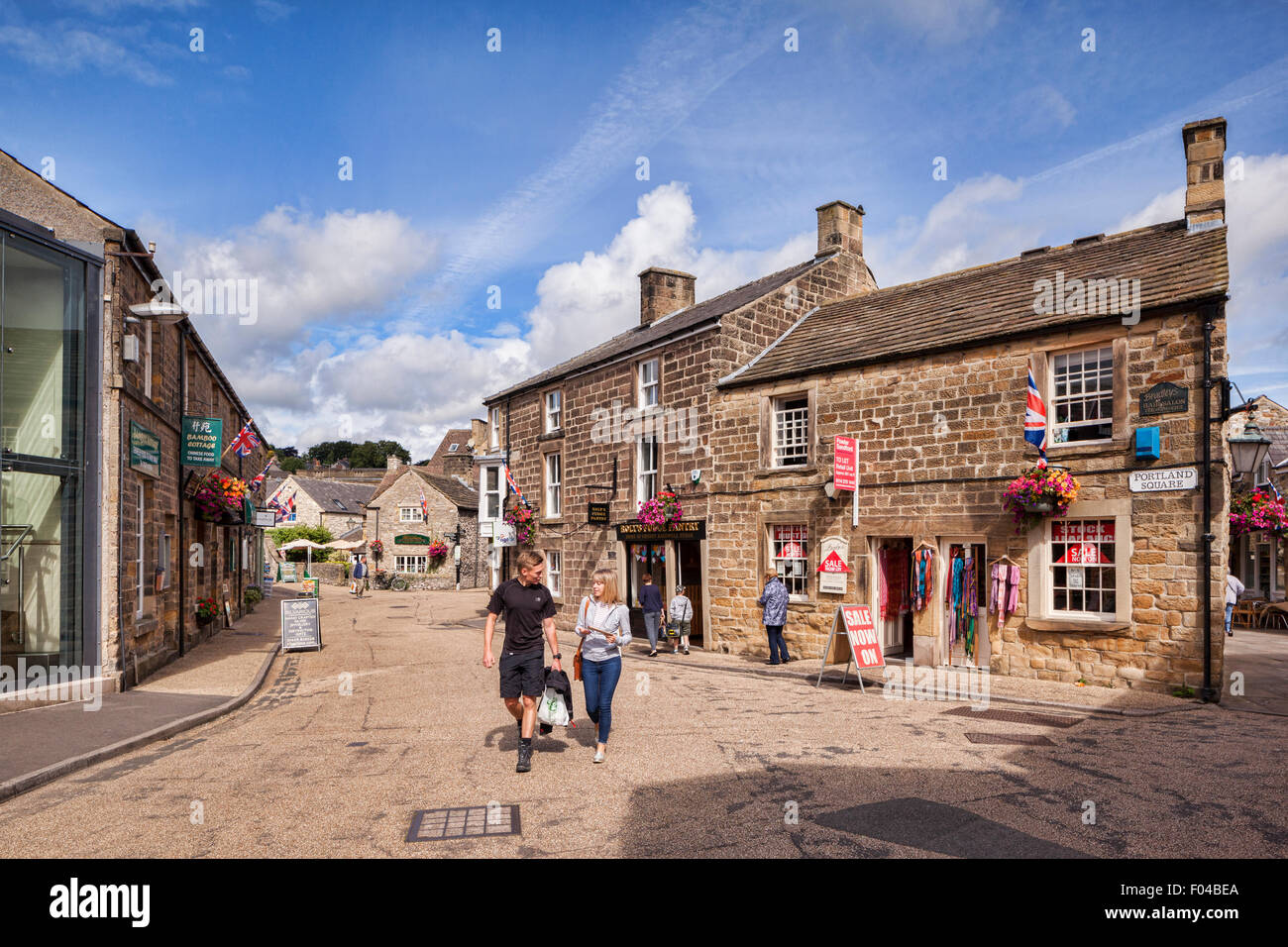 Young couple chatting and walking through Portland Square, Bakewell, Derbyshire, England - Stock Image