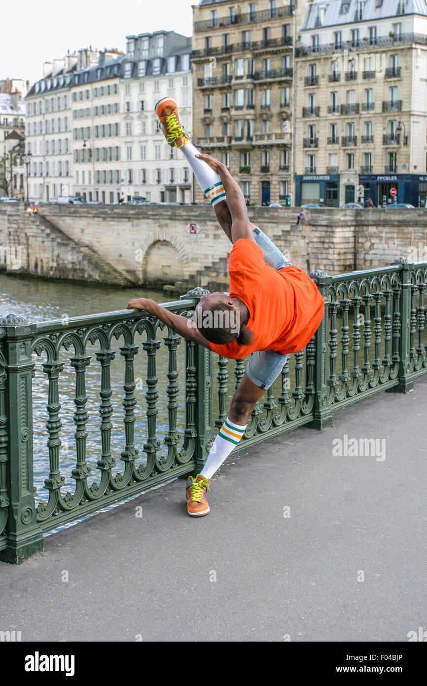 ATHLETIC YOUNG MAN STRETCHING, PARIS,FRANCE - CIRCA 2009. An athletic young man stretching during a warm-up session. - Stock Image