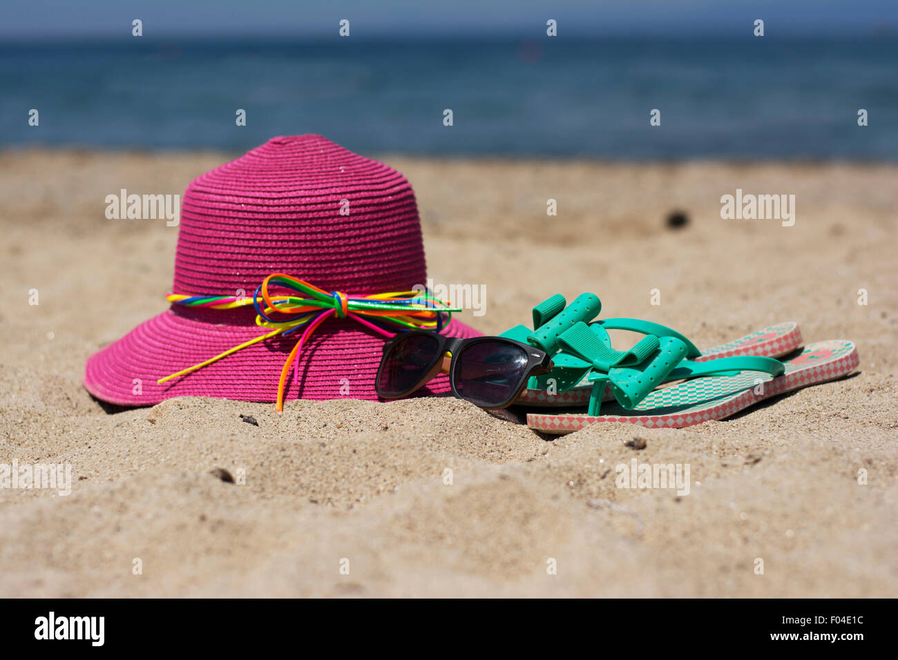 dd632416a5fce0 Summer pink hat and turquoise flip flops on a sandy beach with a sea  background -
