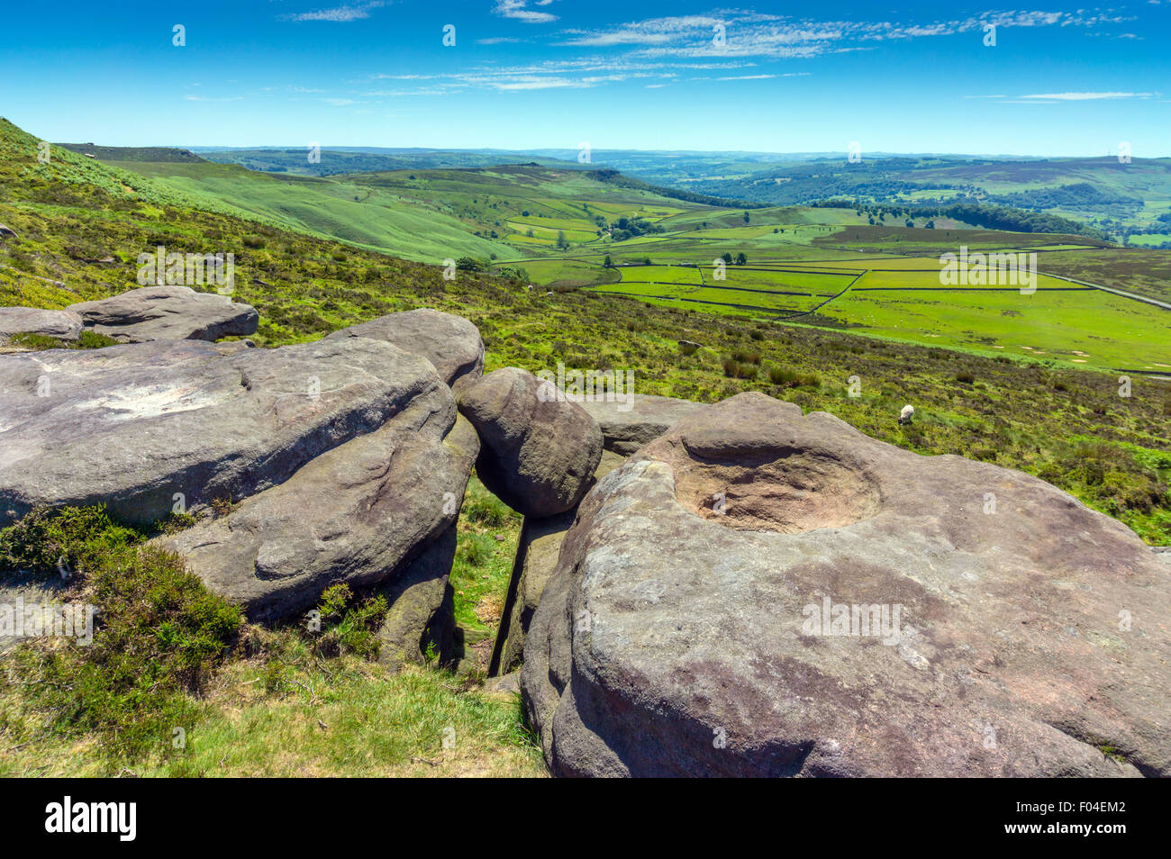 View west from gritstone cliff of Stanage Edge, Peak District, National Park, Derbyshire with boulders in foreground - Stock Image