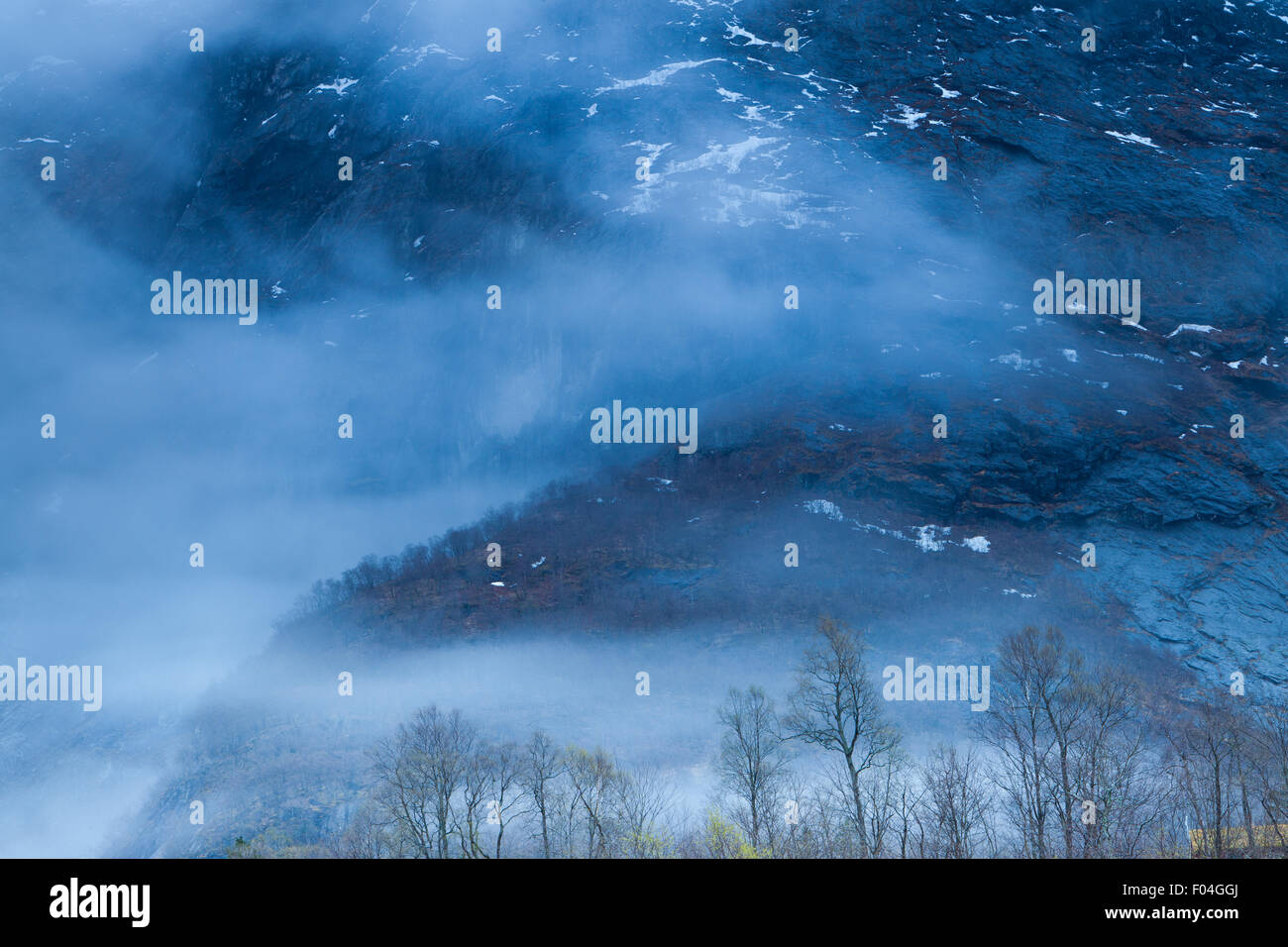 Early morning mist around the mountainsides in the Romsdalen valley, Norway. - Stock Image