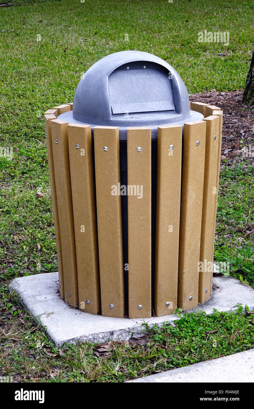 Trash can encased in wood slats in a park - Stock Image
