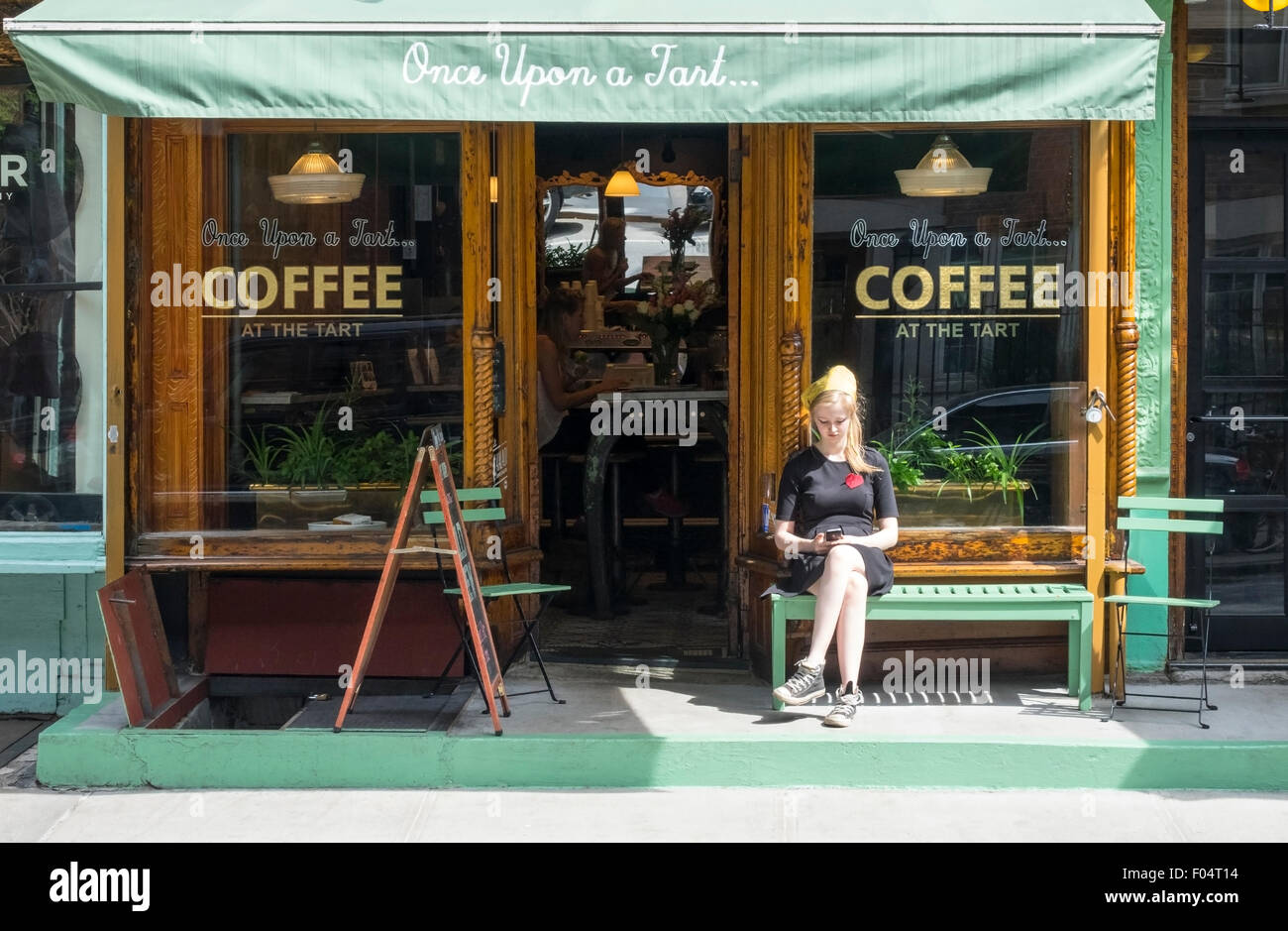 Young blond woman outside the Soho coffeehouse, Once Upon a Tart - Stock Image