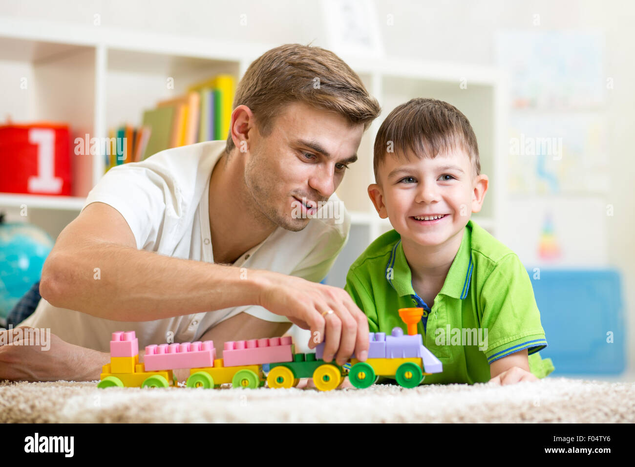 Family time. Kid boy joyfully playing building blocks with his father - Stock Image