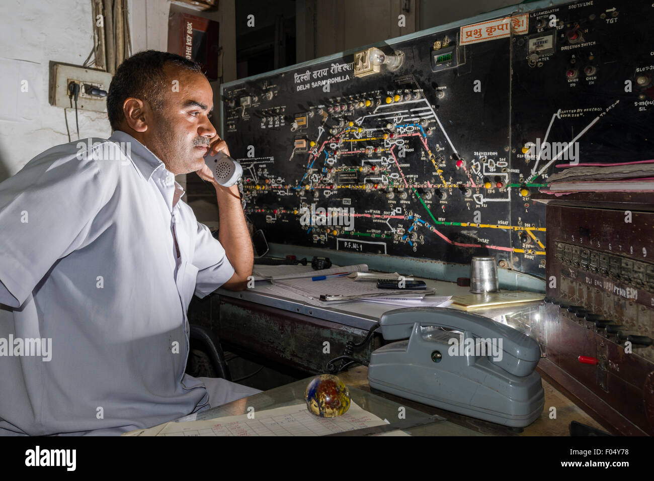 A worker is coordinating the trains arriving and leaving the Railway Station Delhi Sarai Rohilla by hand, New Delhi, - Stock Image