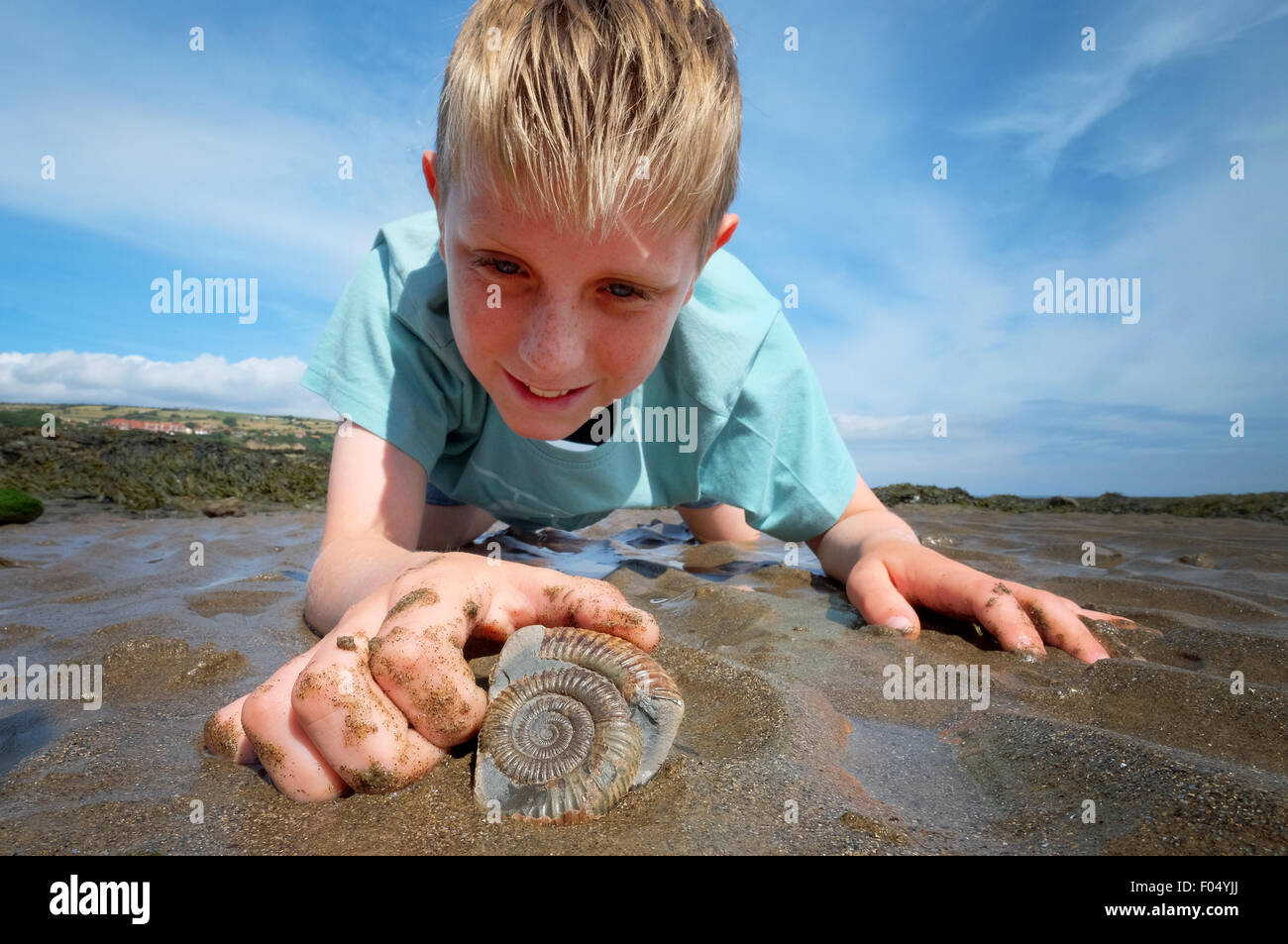 A boy with an ammonite fossil on the Beach at Robin Hood's Bay, part of the Yorkshire Jurassic coast - Stock Image