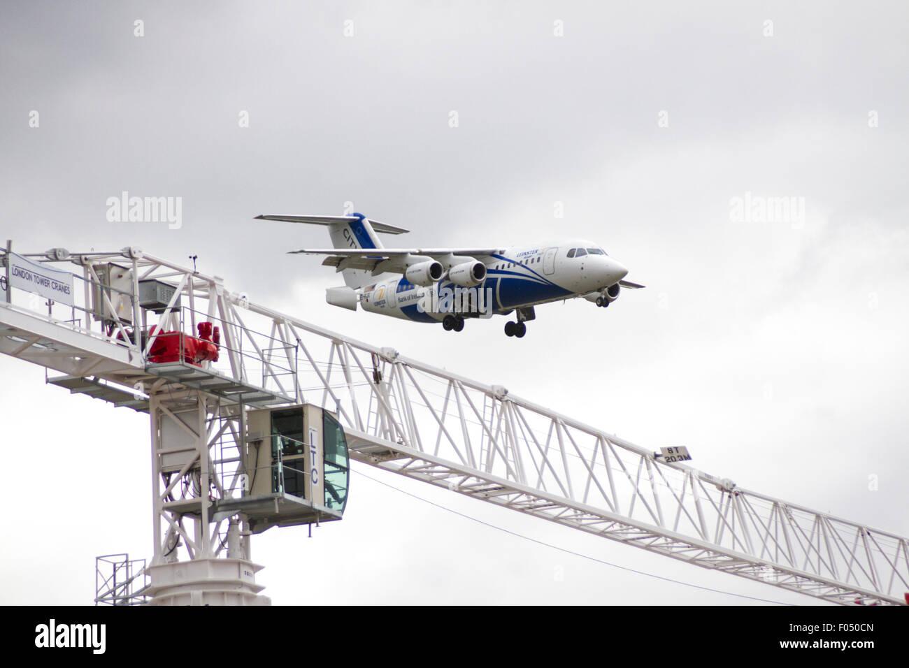 Cityjet Dornier 328-110 landing at City Airport London behind tower crane at Galleons Reach development, Docklands - Stock Image