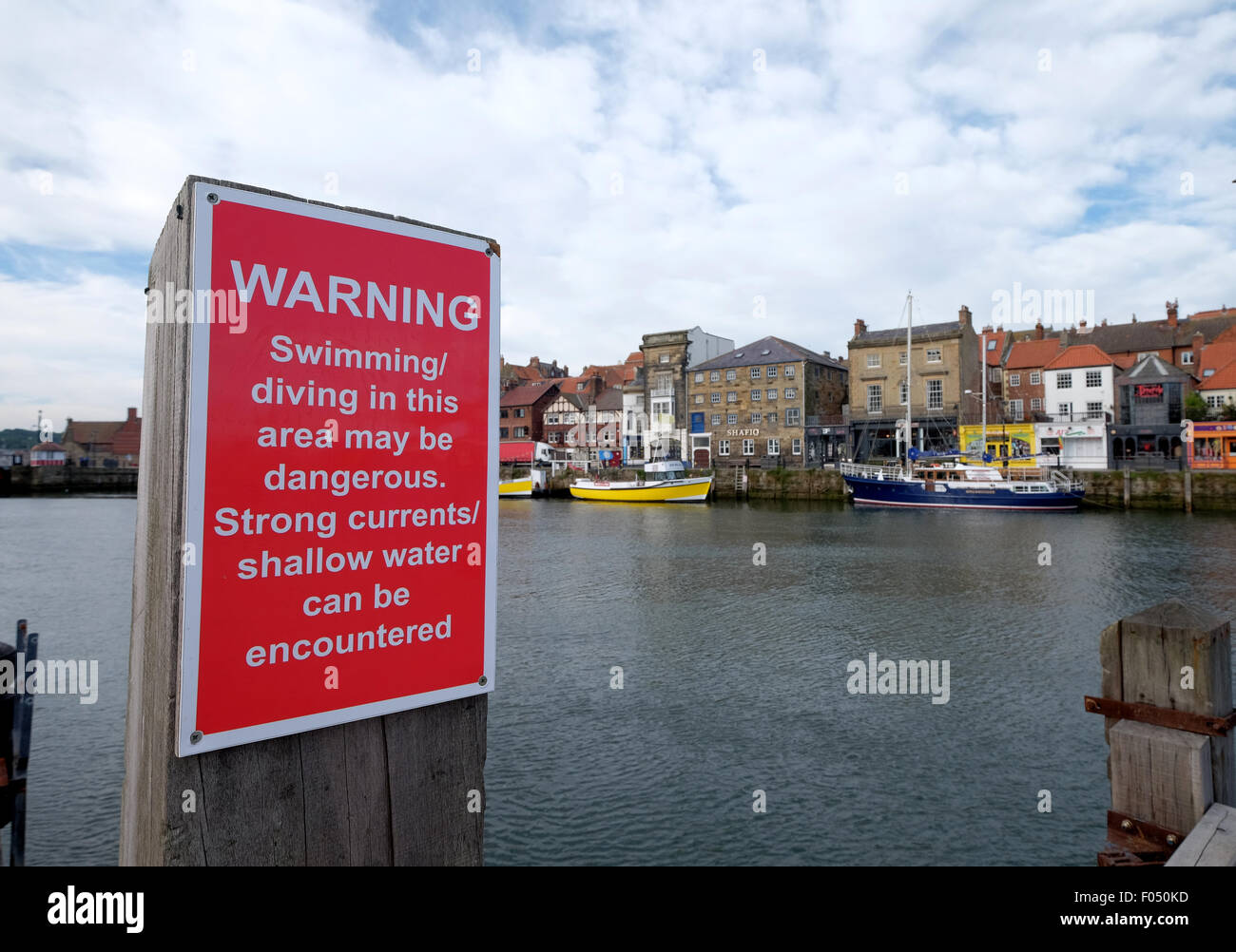Sign warning about the dangers of diving jumping and swimming at Whitby Harbour quayside - Stock Image