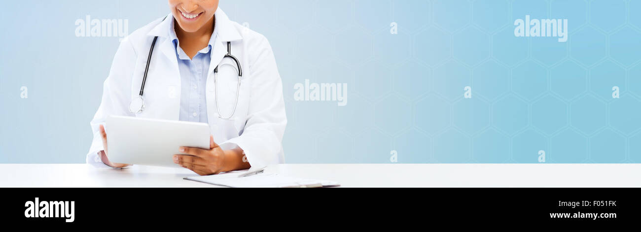 happy african doctor with tablet pc over blue - Stock Image