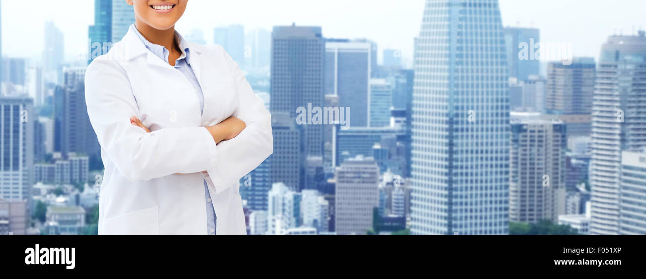 happy african american female doctor over city - Stock Image
