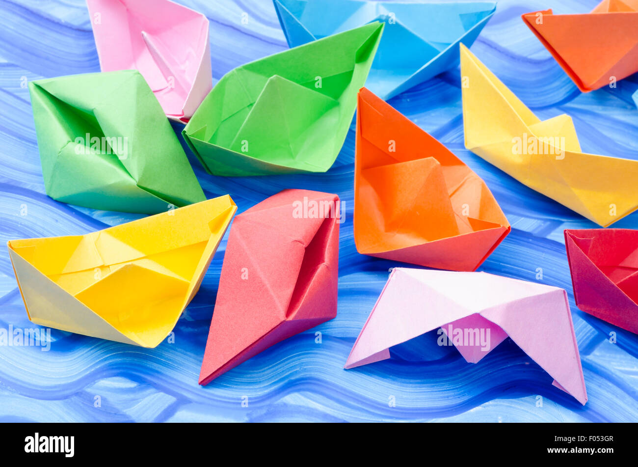 multicolored paper origami boats on blue painted background stock