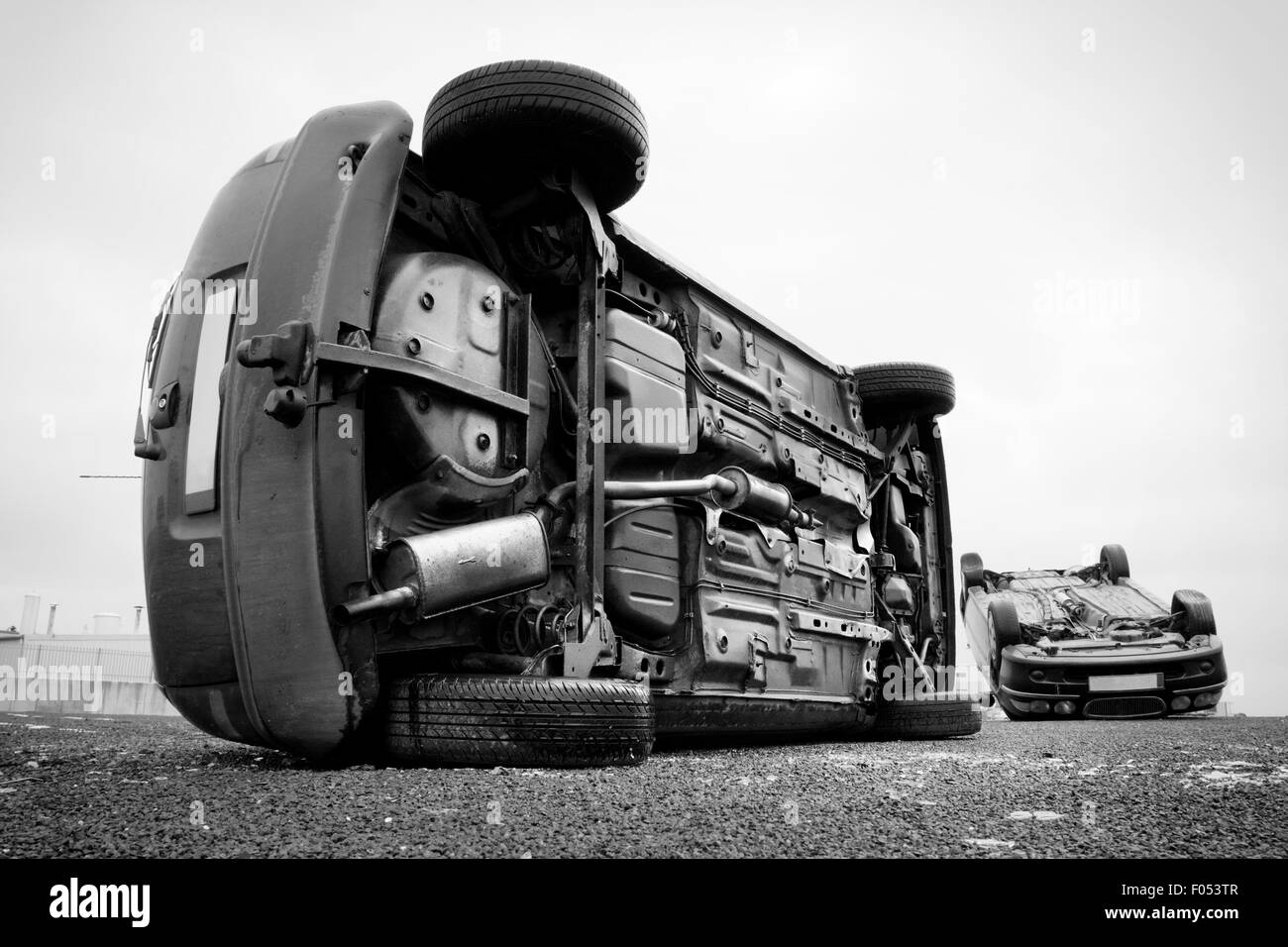 two cars turned upside-down after road collision. Monochromatic Stock Photo