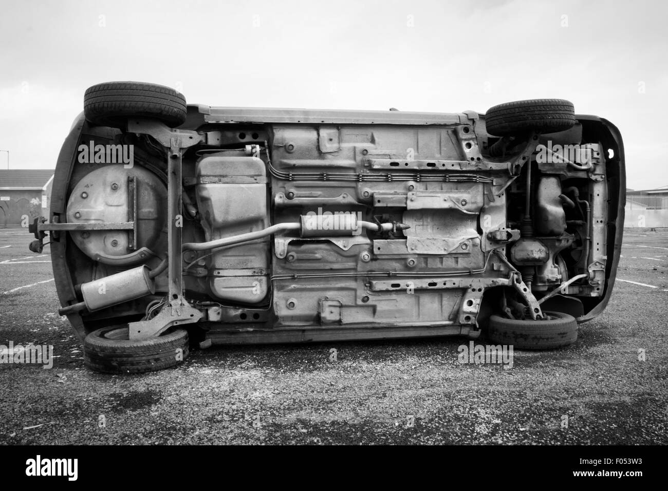car bottom turned on the side after road collision. Monochromatic Stock Photo