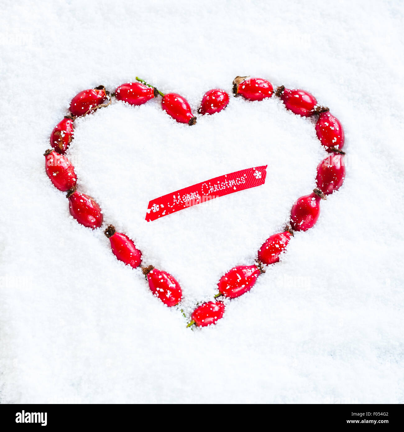 a heart-shaped wreath made with rose hips laid out on the snow, and piece of red ribbon saying Merry Christmas - Stock Image