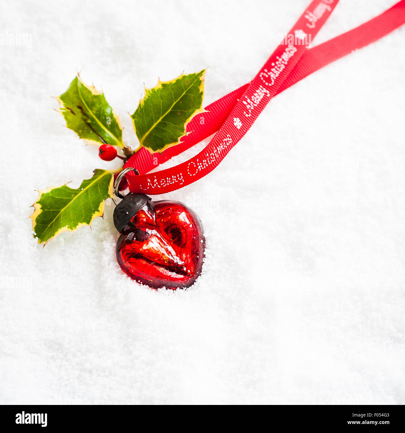 heart shaped red bauble with holly and Merry Christmas ribbon on snow - Stock Image