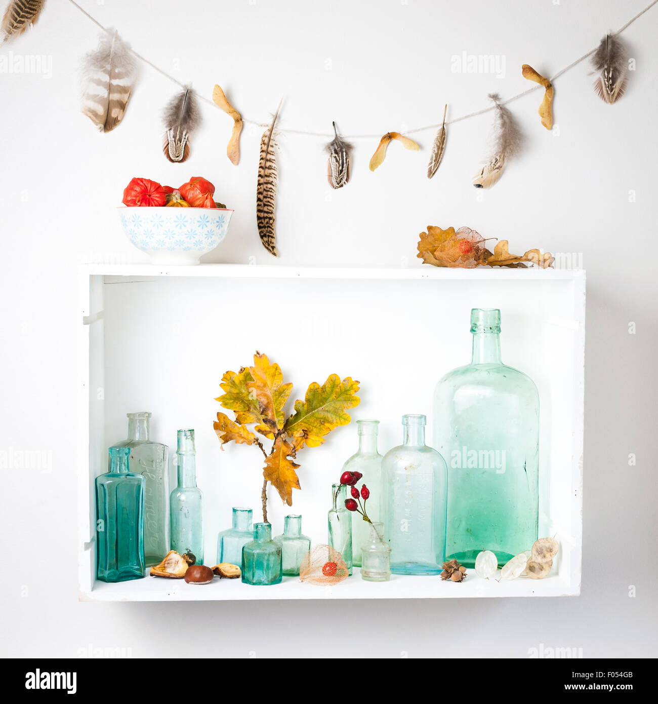 a shelf with a collection of vintage glass bottles  and autumn gatherings, and feather garland - Stock Image
