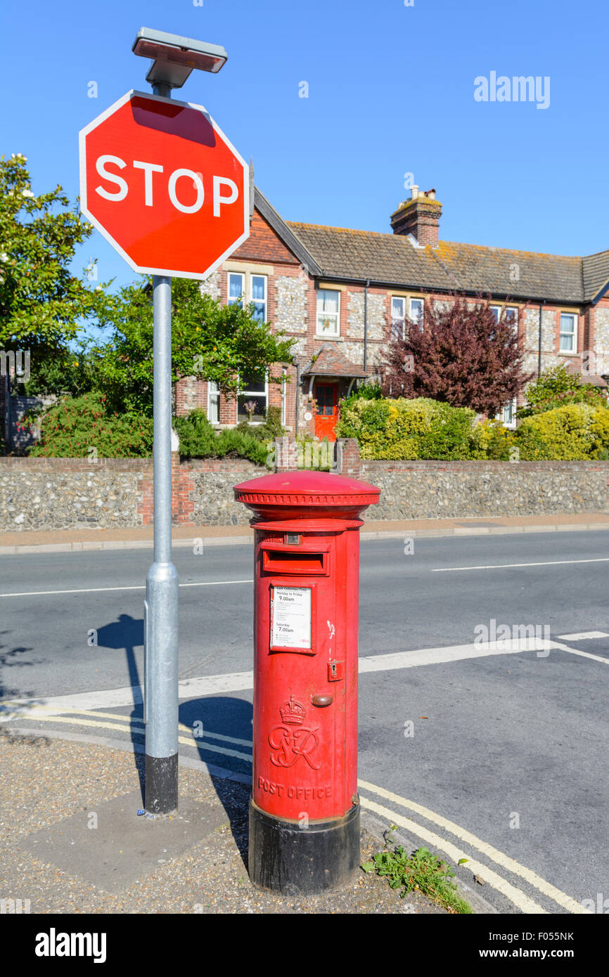 Red letter box. Royal Mail King George VI red Pillar Box on the corner of a road in England, UK. - Stock Image