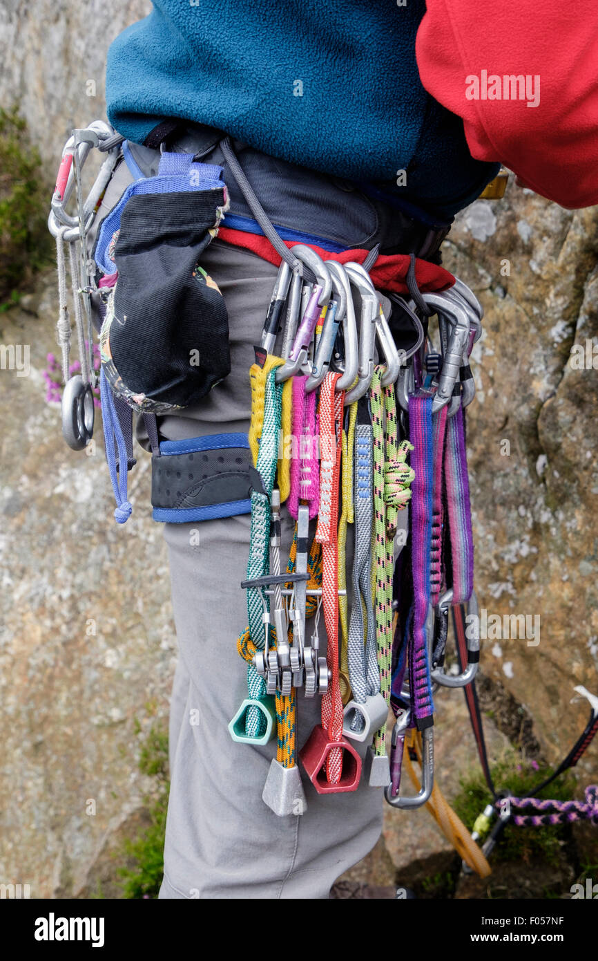 Mountain climber wearing a rock climbing harness with rack of karabiners and chocks. Wales UK Britain - Stock Image