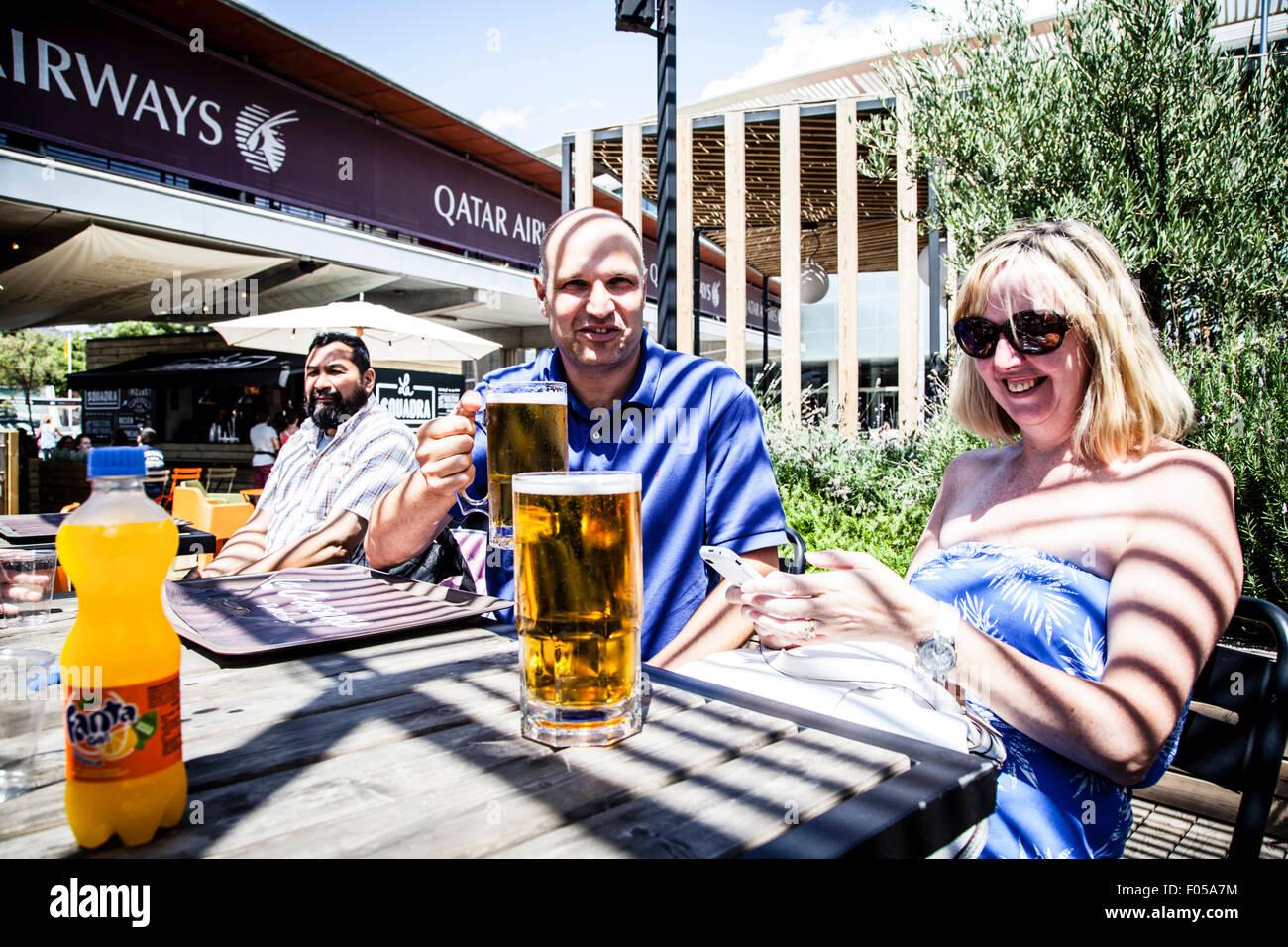 Couple drinking beer outside Barcelona's Stadium, Camp Nou, Barcelona, Spain. - Stock Image