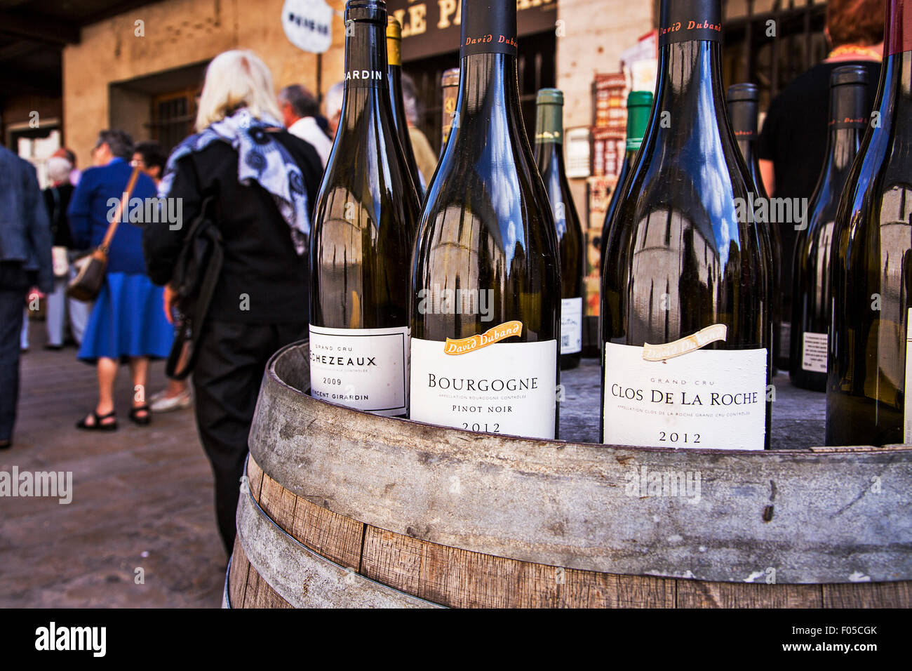 Wine bottles on display at a shop in Beaune hint at the world famous vintages for sale there. - Stock Image