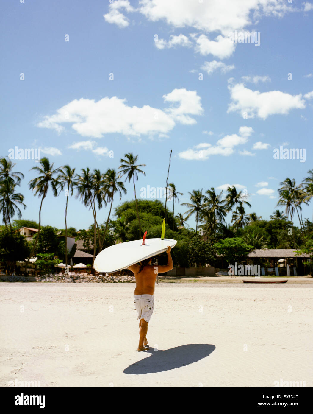 A man brings his wind surfing board in from the ocean. Jericoacoara, Brazil. - Stock Image