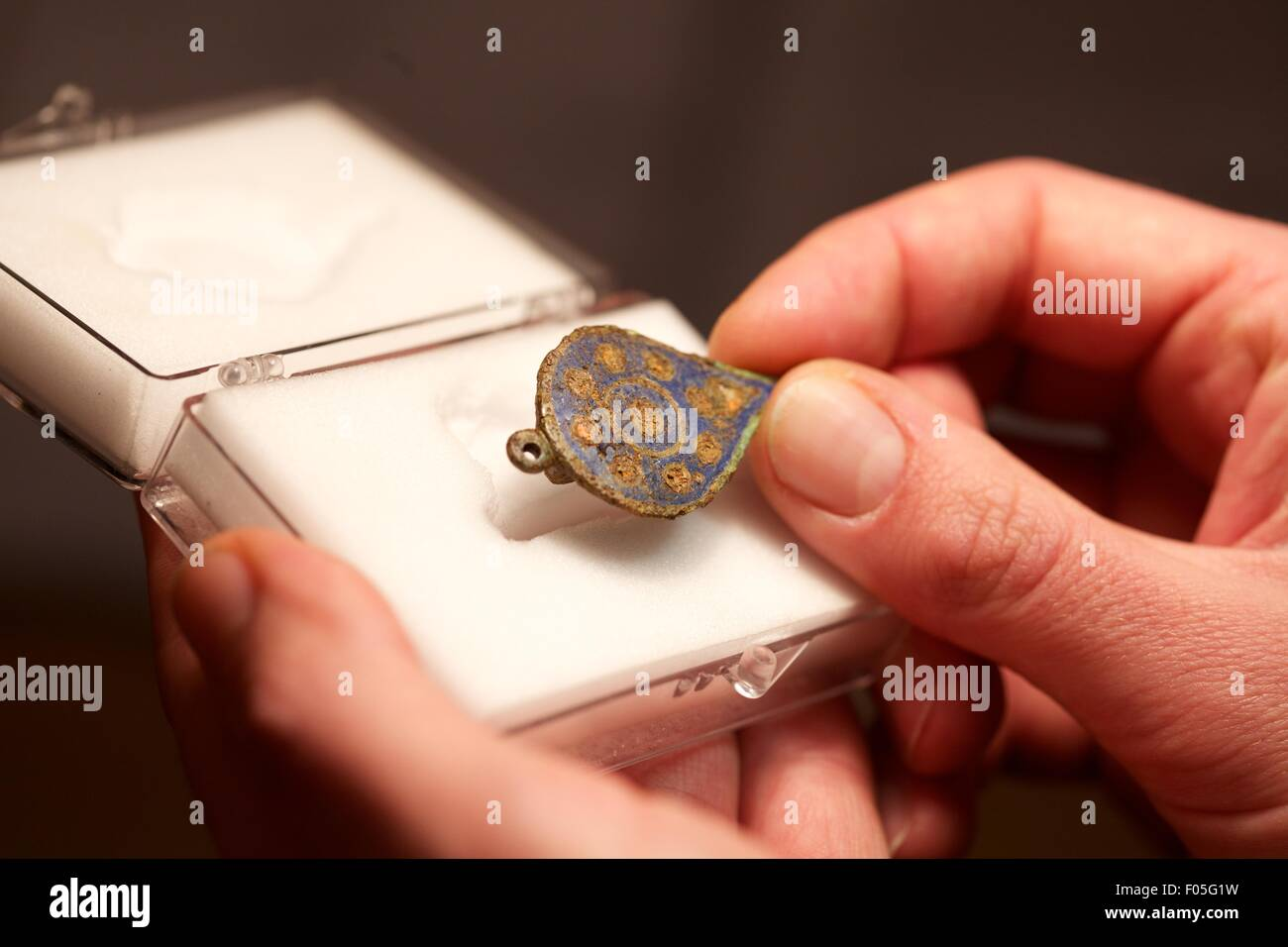 close up shot of hands holding artefact - Stock Image