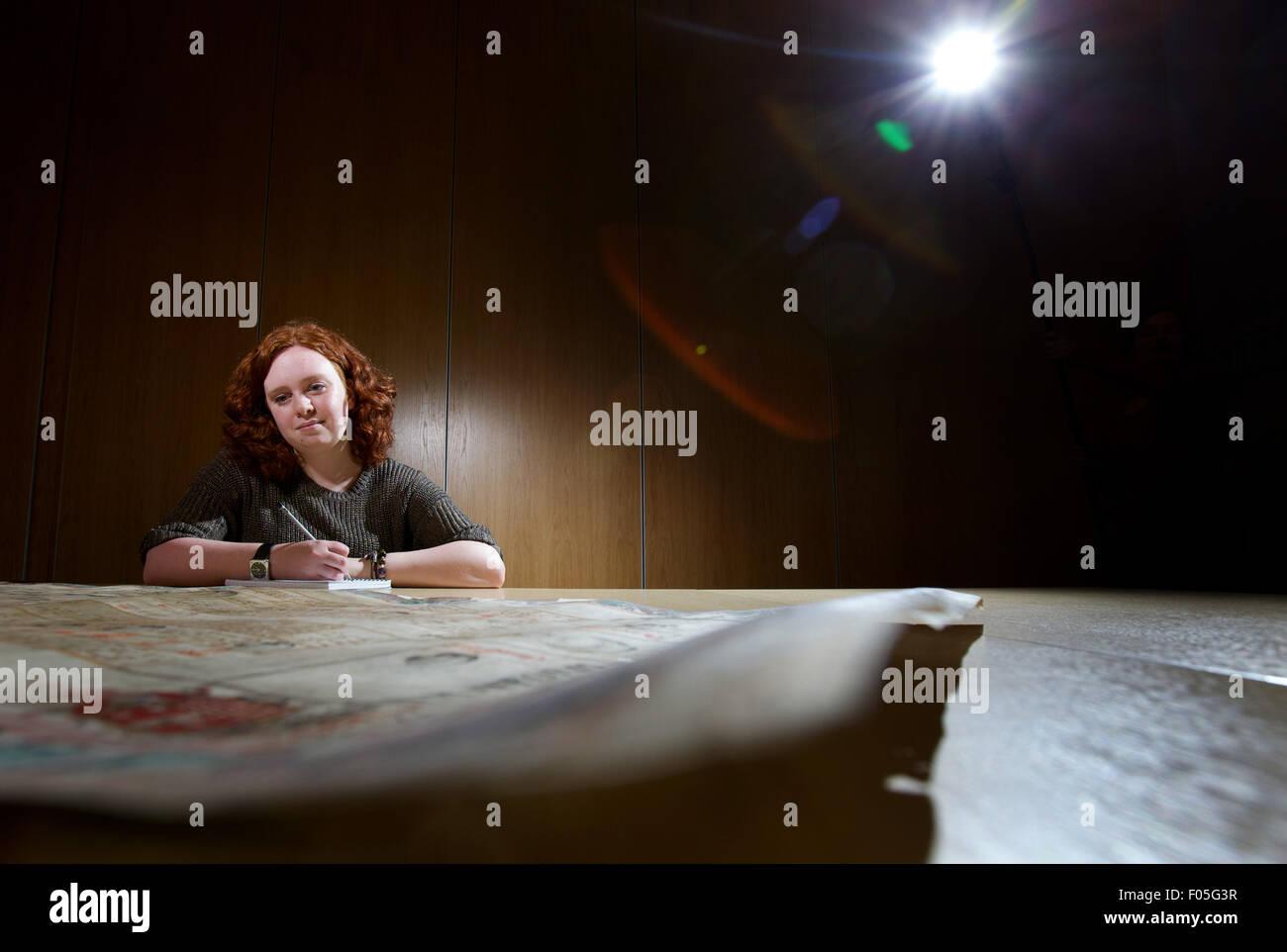 female archeology student studying old maps - Stock Image