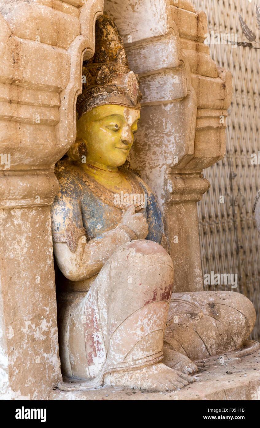 Statue with remnants of original painted colors at Ananda Paya, Bagan, Myanmar - Stock Image