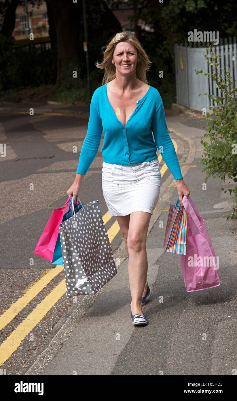 Woman walking in the street carrying paper recyclable carrier shopping bags - Stock Image