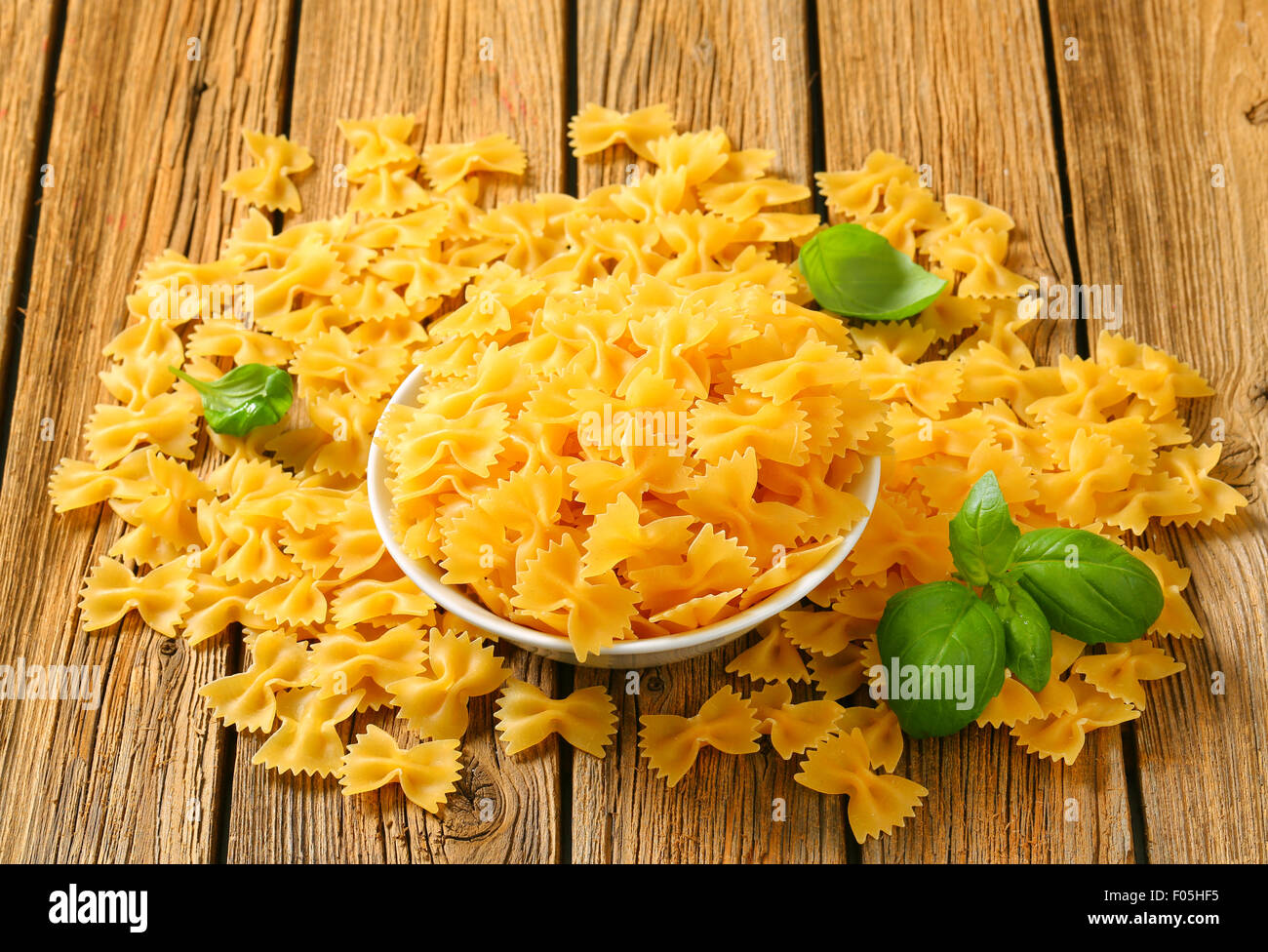 Bowl of uncooked bow tie pasta - Stock Image