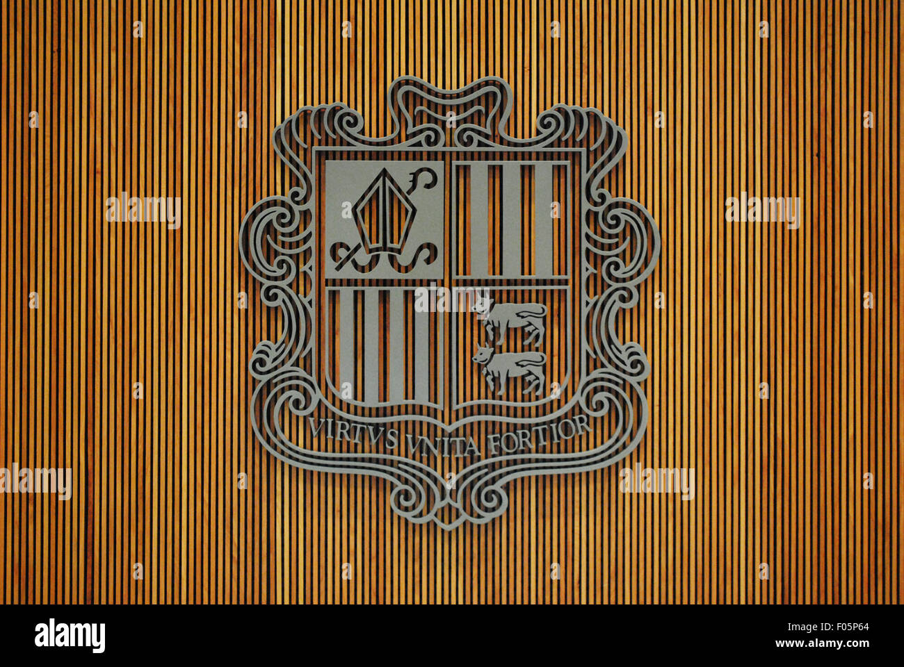 The coat of arms of Andorra against a wooden wall covering. Stock Photo