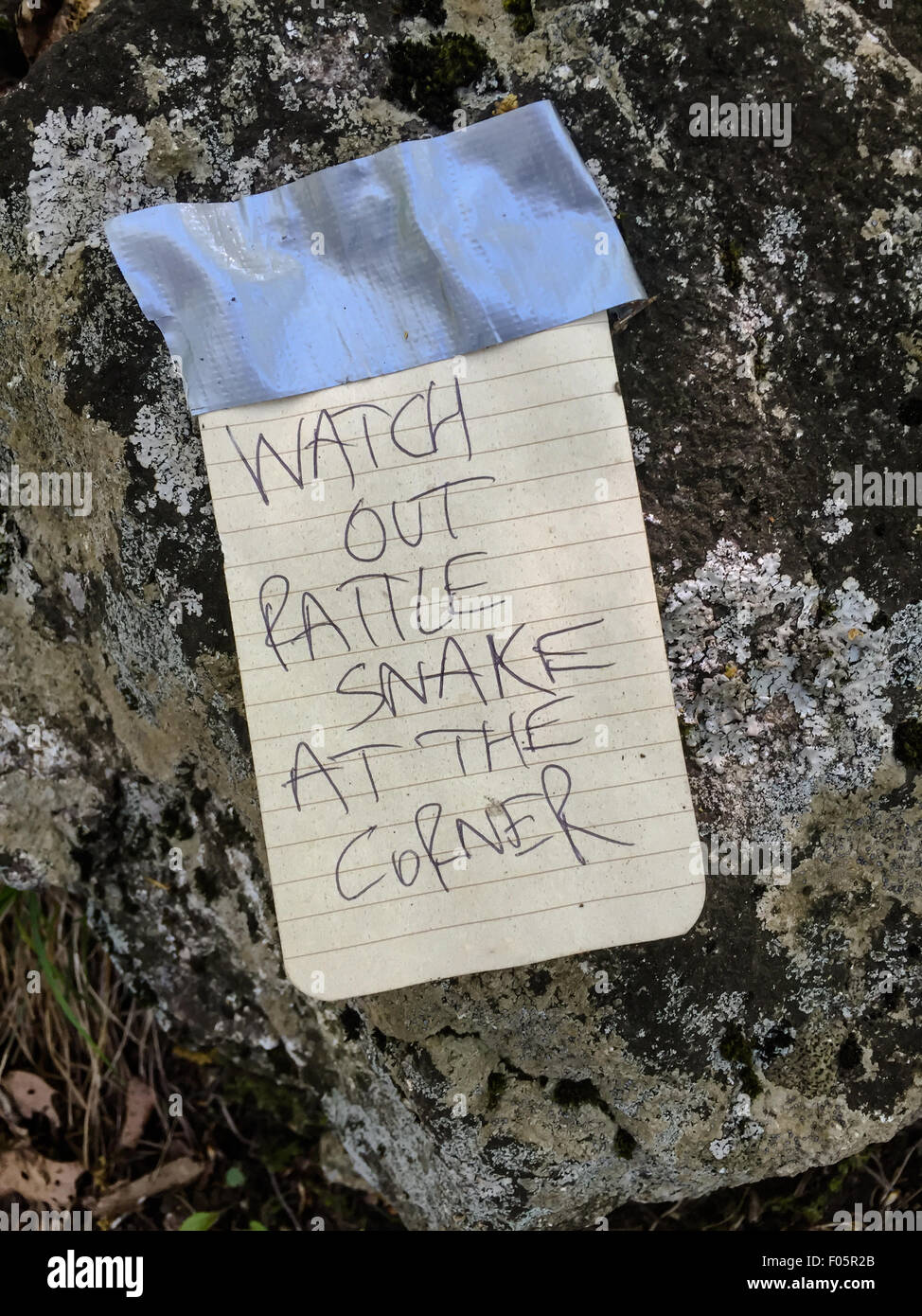 A handwritten note warns hikers of a rattlesnake around the corner - Stock Image