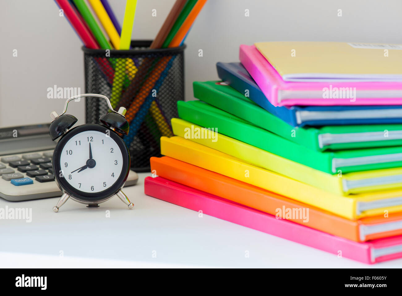 Concept of education. Black alarm clock. Multi colored books in ...