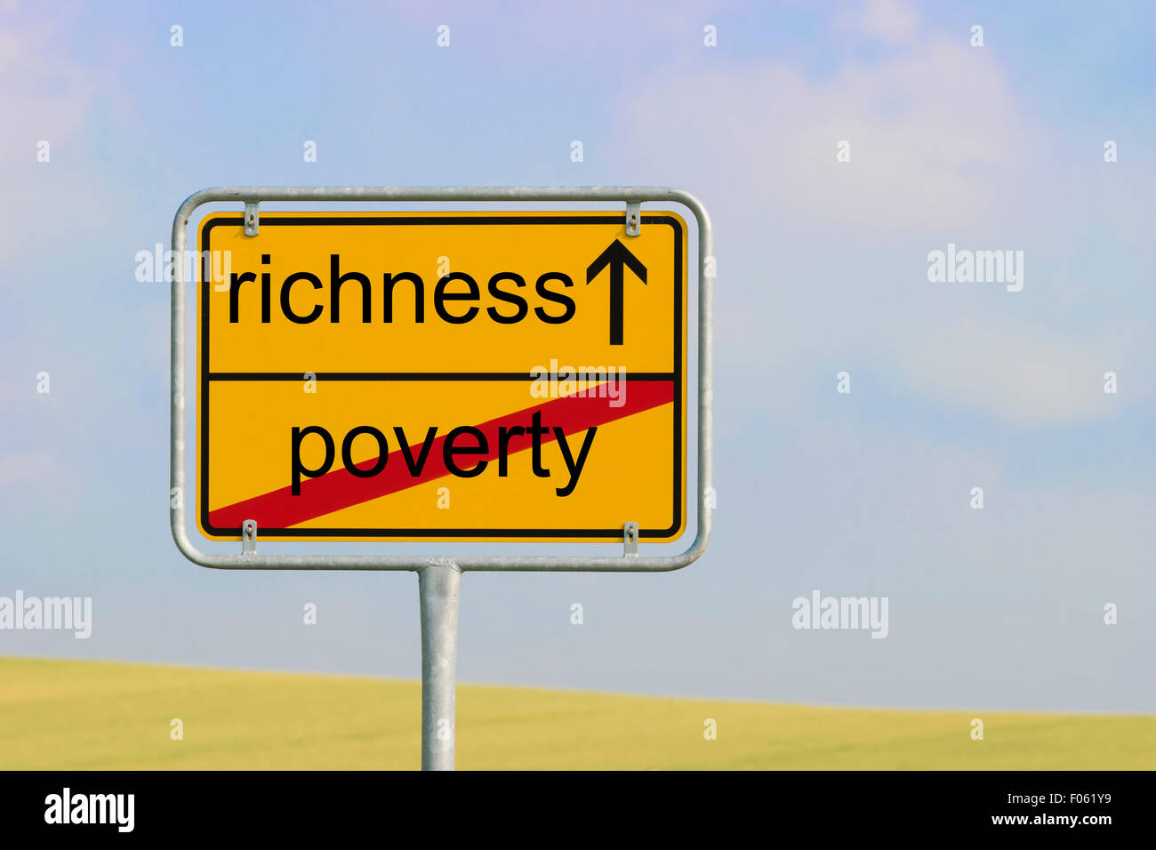 Yellow town sign with text 'poverty richness' - Stock Image