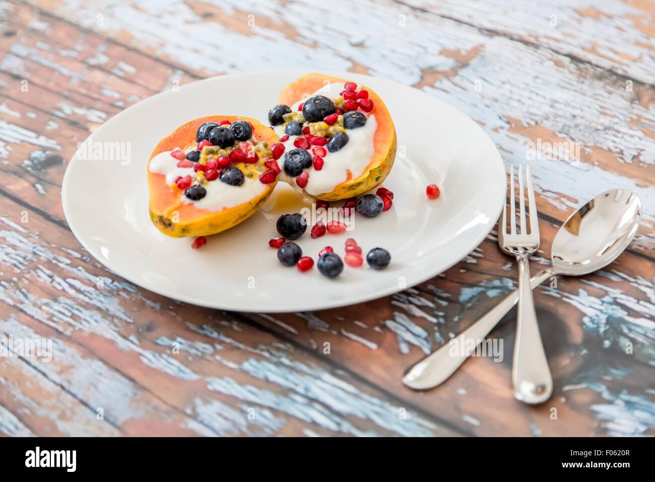papaya with natural soy yogurt and fresh berries, light and healthy breakfast, papaya, blueberries, passion fruit, - Stock Image