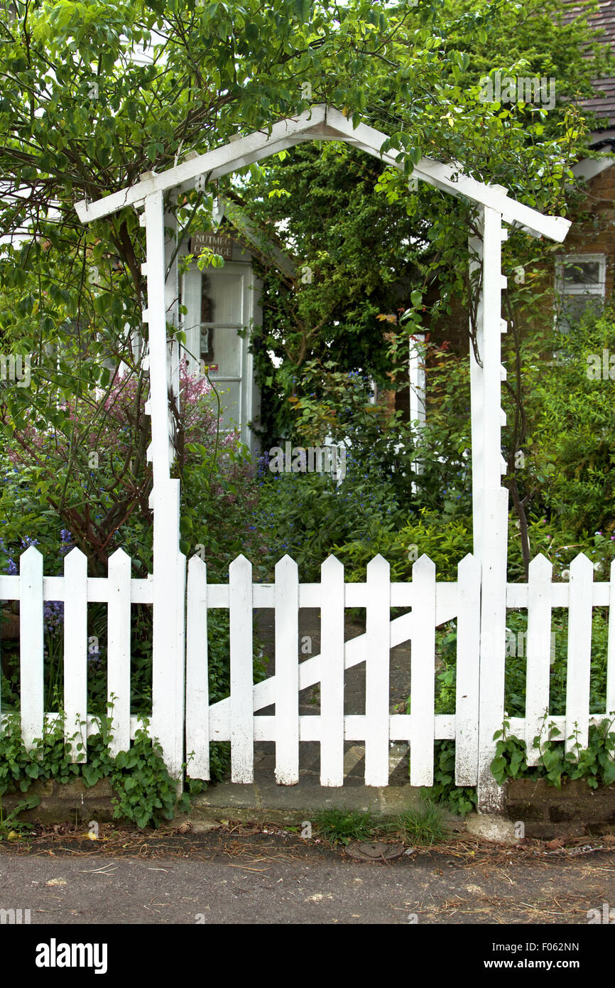 White wooden doorway and picket fence - Stock Image
