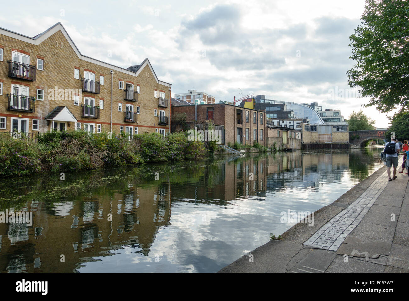 People spending a sunny weekend day in summer 2015 by a canal in East London. - Stock Image