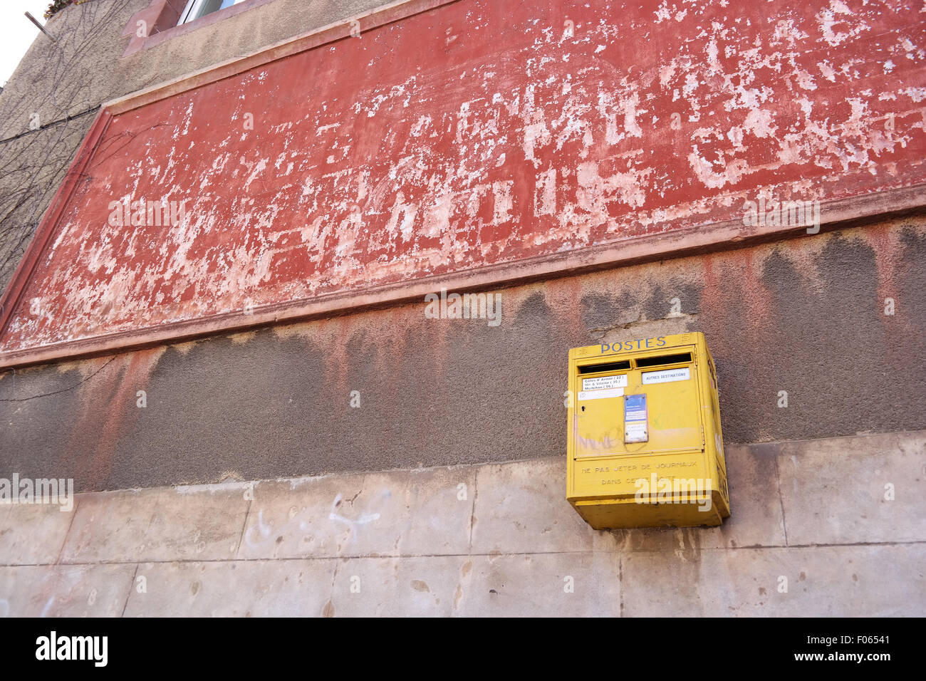 Old yellow French postbox hanging on a wall in Brittany, France. - Stock Image