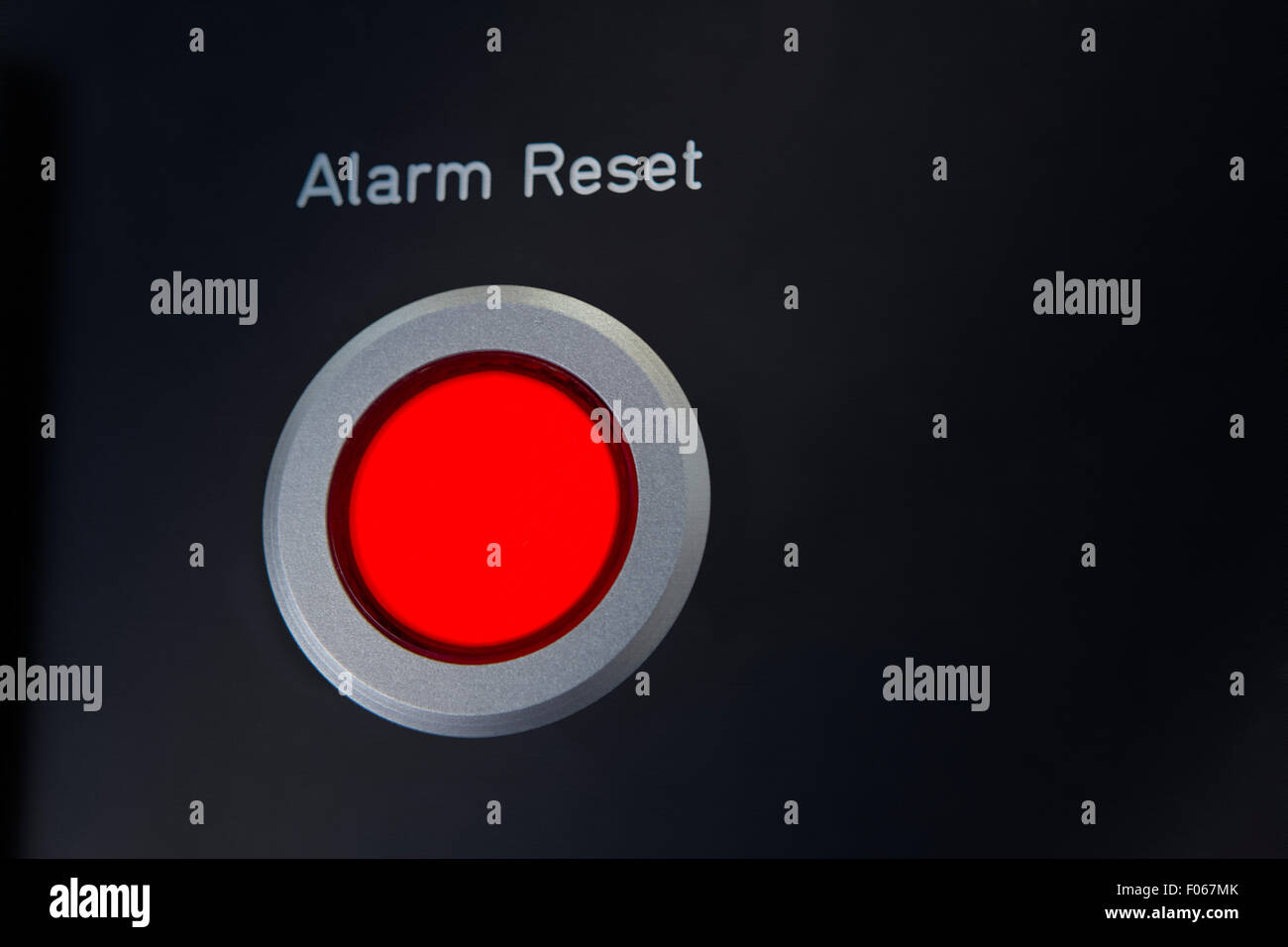 A red Alarm Reset button - Stock Image