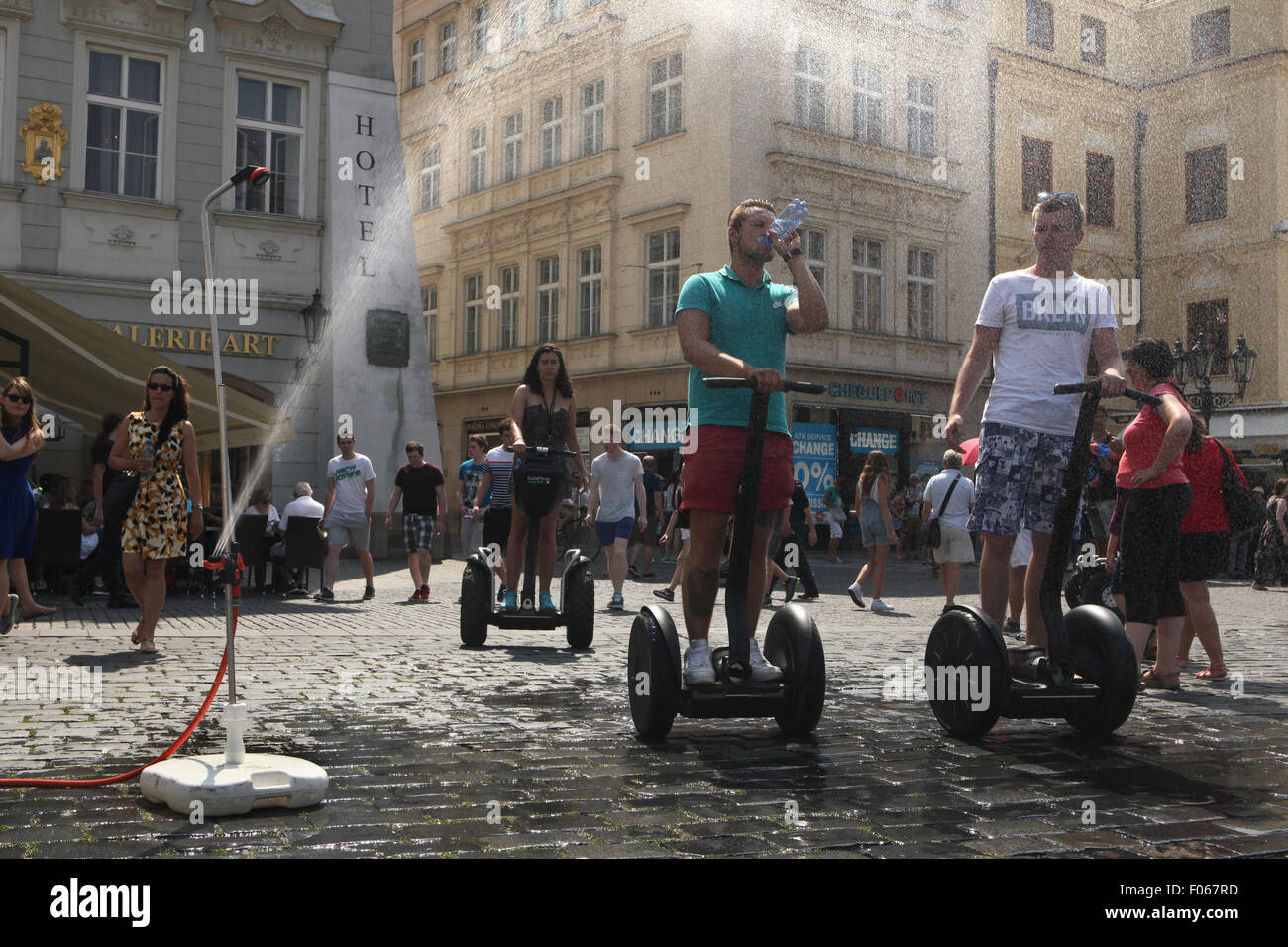 Prague, Czech Republic. 7th August 2015. People riding Segways try to cool off from a water sprinkler installed - Stock Image